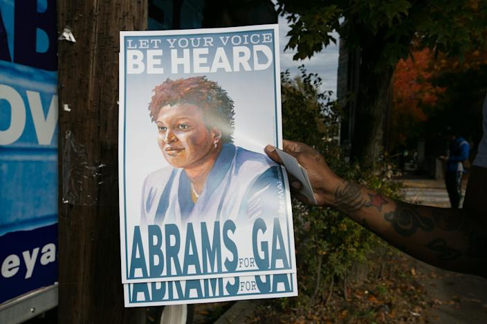 A supporter holds a campaign poster of Democratic Gubernatorial candidate Stacey Abrams outside Busy Bee Cafe on November 6, 2018 in Atlanta, Georgia.