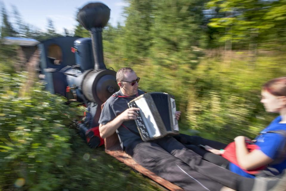 A man plays accordion while riding on Pavel Chilin's miniature steam train in Ulyanovka village outside St. Petersburg, Russia Sunday, July 19, 2020. It took Chilin more than 10 years to build the 350-meter-long miniature personal narrow-gauge railway complete with various branches, dead ends, circuit loops, and even three bridges.(AP Photo/Dmitri Lovetsky)