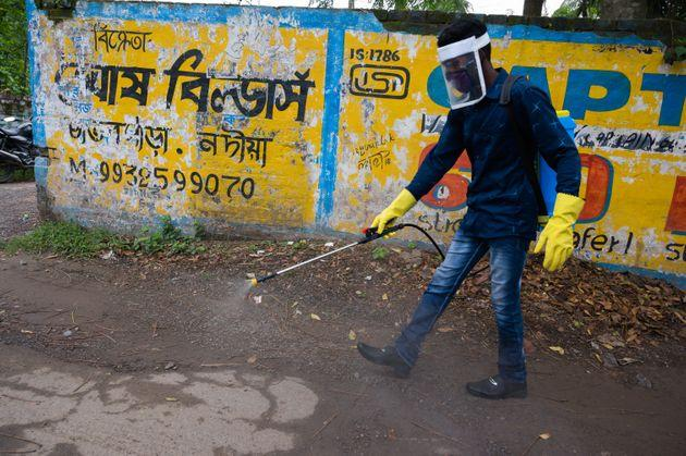 Member of the cleaning staff disinfect a street in Tehatta, Nadia, West Bengal, India on May 27, 2020. (Photo by Soumyabrata Roy/NurPhoto via Getty Images)