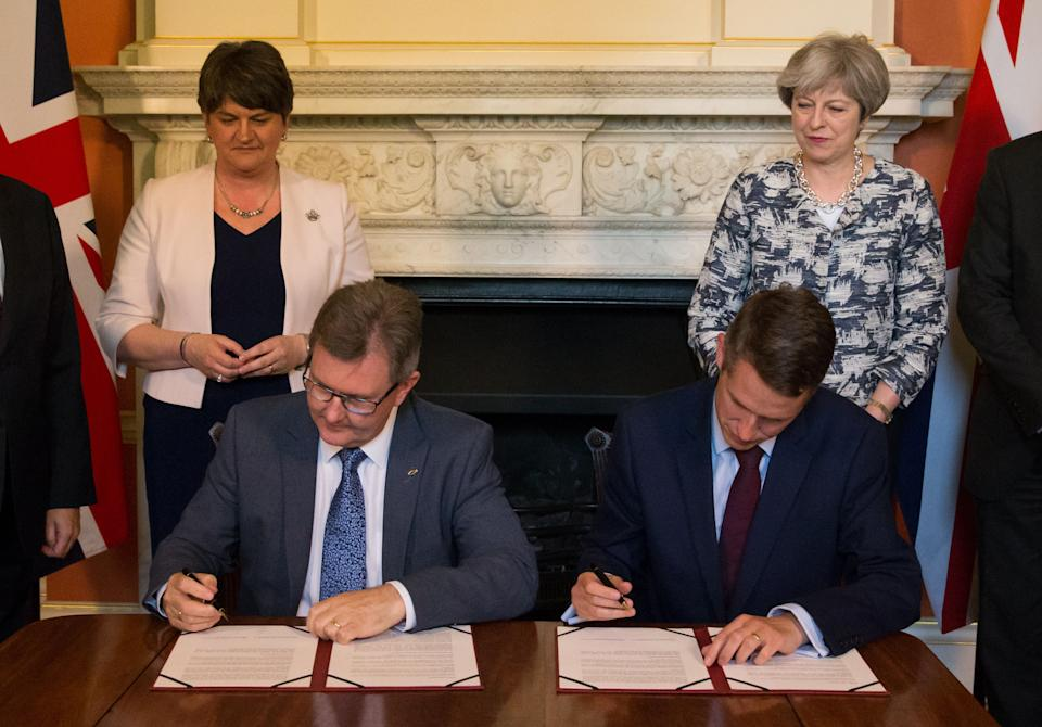 File photo dated 26/06/17 of Prime Minister Theresa May standing with DUP leader Arlene Foster (left), as DUP MP Sir Jeffrey Donaldson (second right) and Parliamentary Secretary to the Treasury, and Chief Whip, Gavin Williamson, sign paperwork inside 10 Downing Street, London, after the DUP agreed a deal to support the minority Conservative government. The Prime Minister is expected to announce details later today of her timetable for leaving Downing Street.