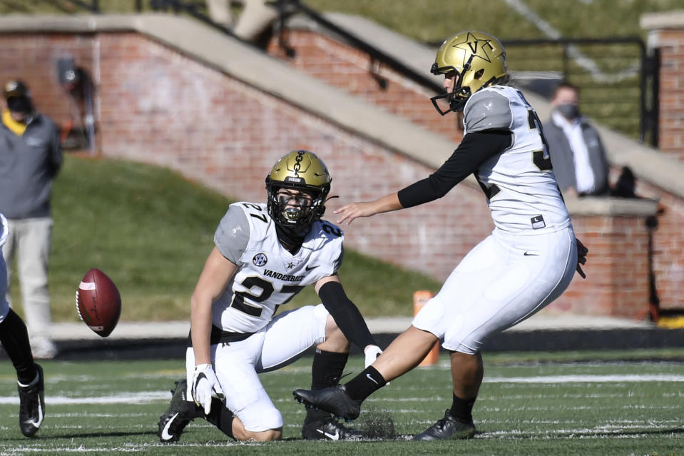 Vanderbilt's Sarah Fuller, right, kicks off as Ryan McCord (27) holds to start the second half of an NCAA college football game against Missouri Saturday, Nov. 28, 2020, in Columbia, Mo. With the kick, Fuller became the first female to play in a Southeastern Conference football game. (AP Photo/L.G. Patterson)