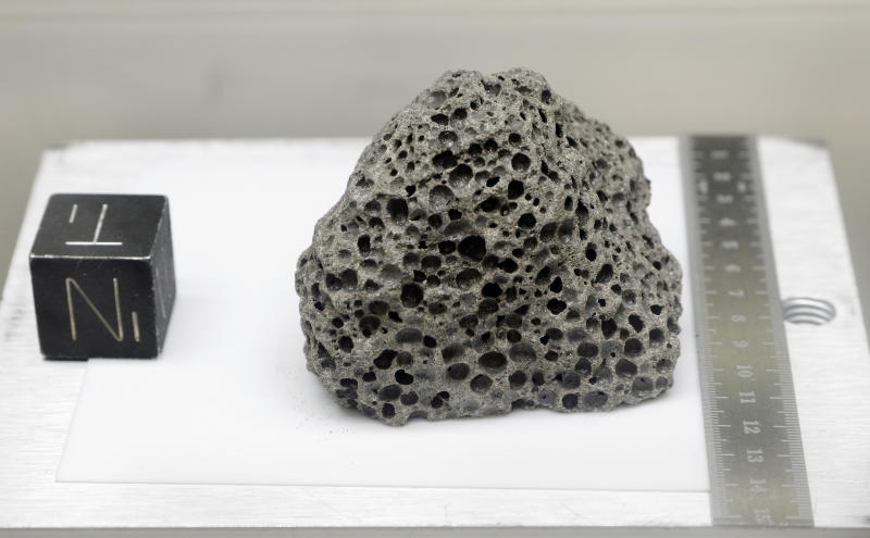 Collected during Apollo 15, a 3.5 billion years old basalt rock similar to rocks formed around Hawaii, is displayed in a pressurized nitrogen-filled examination case inside the lunar lab at the NASA Johnson Space Center Monday, June 17, 2019, in Houston. For the first time in decades, NASA is about to open some of the pristine samples and let geologists take a crack at them with 21st-century technology. (Photo: Michael Wyke/AP)