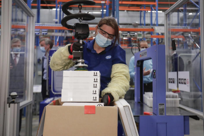 A worker uses a machine to pack boxes of the Pfizer COVID-19 vaccine doses during an official visit by Belgium's King Philippe to the Pfizer vaccine production site in Puurs, Belgium, Tuesday, March 30, 2021. (Stephanie Lecocq, Pool via AP)