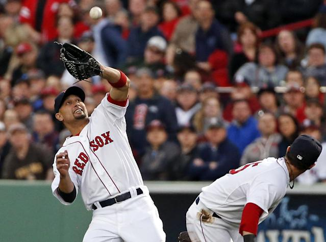 Boston Red Sox second baseman Dustin Pedroia, right, ducks out of the way as right fielder Shane Victorino catches a fly ball by Cincinnati Reds' Zack Cozart during the second inning of a baseball game at Fenway Park in Boston, Tuesday, May 6, 2014. (AP Photo/Elise Amendola)