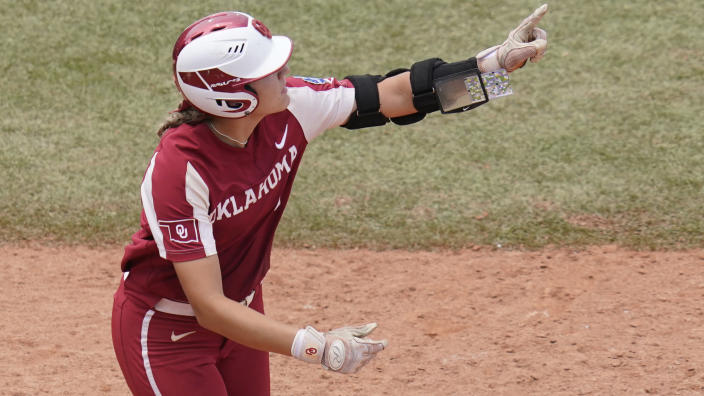 Oklahoma's Kinzie Hansen gestures as she runs toward first base after hitting a home run in the seventh inning against James Madison in an NCAA Women's College World Series softball game Sunday, June 6, 2021, in Oklahoma City. (AP Photo/Sue Ogrocki)