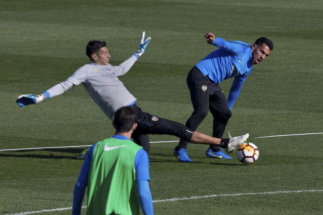 Boca Junior's Carlos Tevez, right, is challenged by goalkeeper Esteban Andrade during a training session in Madrid, Spain, Thursday, Dec. 6, 2018. The Copa Libertadores Final will be played on Dec. 9 in Spain at Real Madrid's stadium for security reasons after River Plate fans attacked the Boca Junior team bus heading into the Buenos Aires stadium for the meeting of Argentina's fiercest soccer rivals last Saturday. (AP Photo/Paul White)