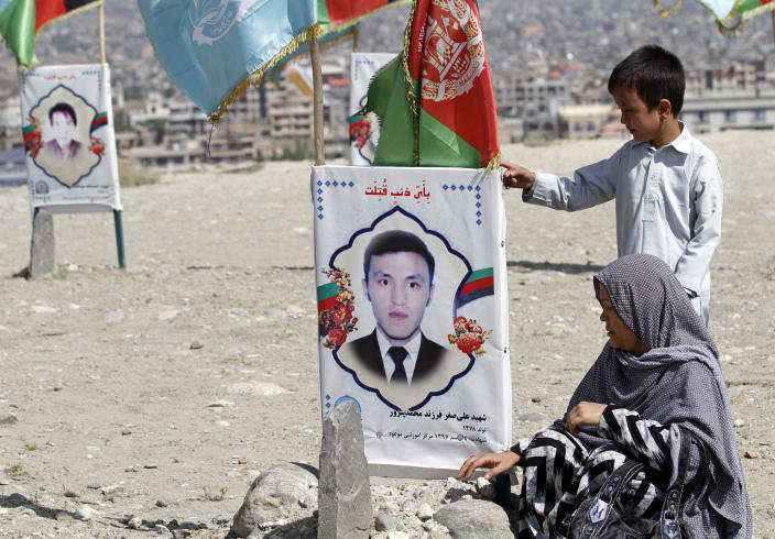 An Afghan woman site near to the grave of her son, adorned with his picture, on the outskirts of Kabul, Afghanistan, Monday, Sept 14, 2020. Scores of friends and families of students who were killed in local conflicts are gathering in a cemetery to call for a permanent countrywide ceasefire from the parties to the intra-Afghan peace conference taking place in Doha, Qatar. (AP Photo/Rahmat Gul)