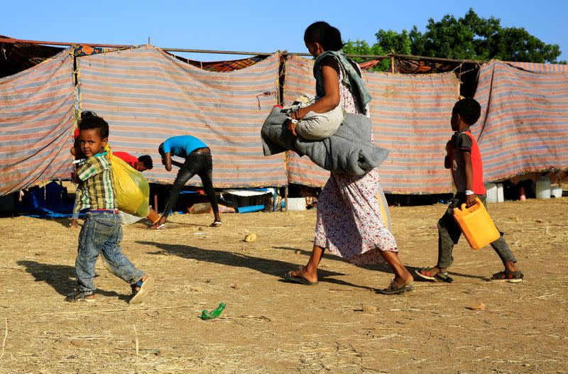 An Ethiopian woman and her children who fled war in Tigray region, carry their belongings as they arrive at the Um-Rakoba camp, on the Sudan-Ethiopia border in Al-Qadarif state