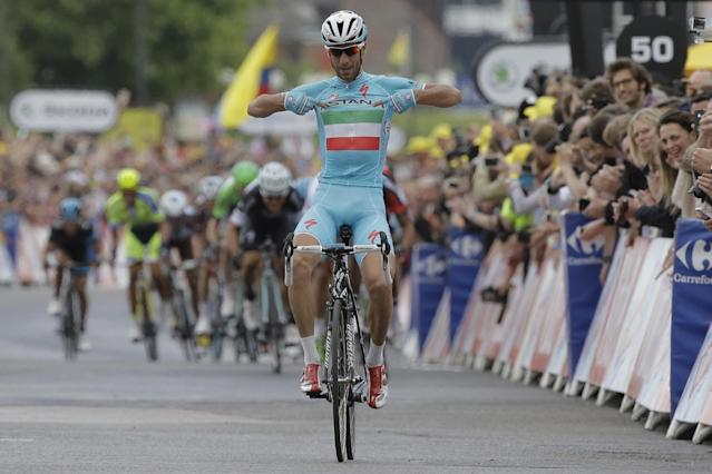 Italy's Vincenzo Nibali points to his shirt as he crosses the finish line ahead of the sprinting pack to win the second stage of the Tour de France cycling race over 201 kilometers (124.9 miles) with start in York and finish in Sheffield, England, Sunday, July 6, 2014. (AP Photo/Laurent Cipriani)
