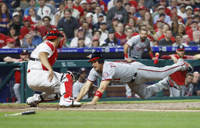 Washington Nationals' Ryan Zimmerman, right, tries to dive into home but is tagged out by Philadelphia Phillies catcher J.T. Realmuto, left, during the fourth inning of a baseball game, Monday, April 8, 2019, in Philadelphia. (AP Photo/Chris Szagola)