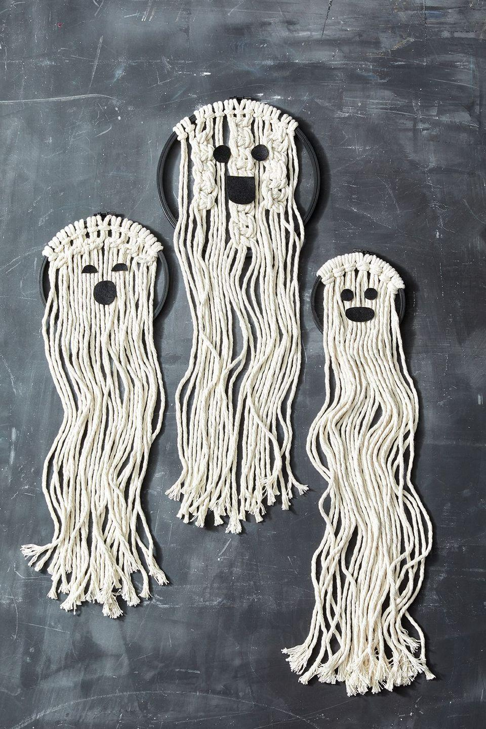 """<p>These friendly little ghosts can be created totally last-minute. Begin by painting embroidery hoops with black paint and let dry. Cut equal lengths of macrame cord about 50"""" long (you will need 12 - 14 pieces of cord per hoop).</p><p><strong>Follow instructions below for simple knots or make your own:</strong></p><ul><li>Lark's Head Knot: hold 2 pieces of cord together and fold in half. Wrap the folded half around the embroidery hoop and pull all 4 tails through the loop. Pull tight to secure. Repeat around the top of the hoop.</li><li>Square Knot: Start by creating Lark's Head knots with one cord each across the top of the hoop. Starting with leftmost piece, wrap it over the next 2 cords to the right. Then take the 4th cord and wrap it behind the previous two cords on the left, tucking it through the space between the first 2 cords. Pull to tighten. Continue across the embroidery hoop.</li></ul><p><a class=""""link rapid-noclick-resp"""" href=""""https://www.amazon.com/Caydo-Embroidery-Circle-Stitch-Sewing/dp/B07L3D4R59?tag=syn-yahoo-20&ascsubtag=%5Bartid%7C10055.g.421%5Bsrc%7Cyahoo-us"""" rel=""""nofollow noopener"""" target=""""_blank"""" data-ylk=""""slk:SHOP EMBROIDERY HOOPS"""">SHOP EMBROIDERY HOOPS</a></p>"""