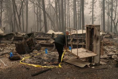 FILE PHOTO: A Butte County Sheriff deputy places yellow tape at the scene where human remains were found during the Camp fire in Paradise