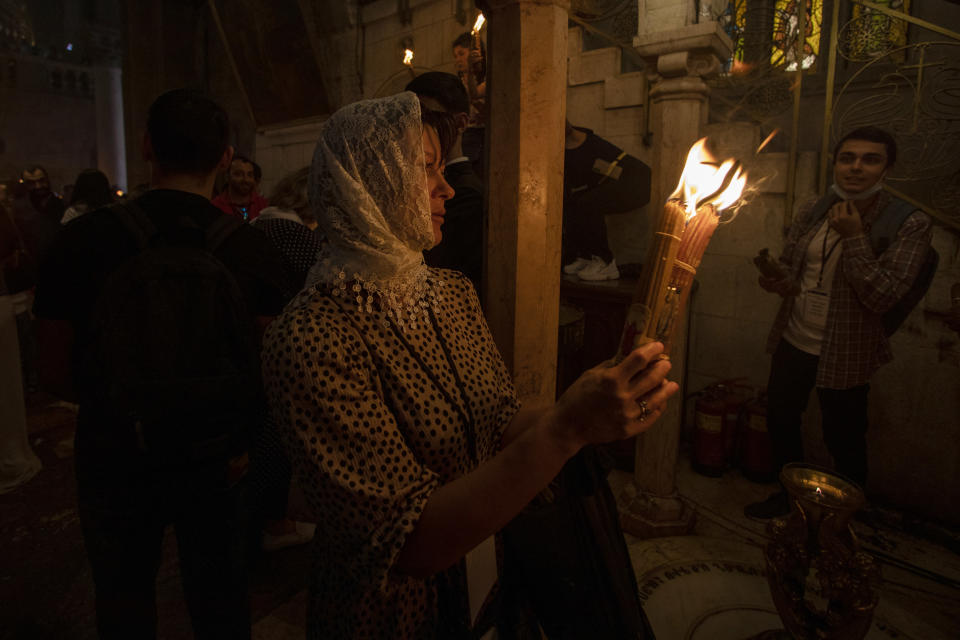 A Christian pilgrim holds candles during the ceremony of the Holy Fire at Church of the Holy Sepulchre, where many Christians believe Jesus was crucified, buried and rose from the dead, in the Old City of Jerusalem, Saturday, May 1, 2021. Hundreds of Christian worshippers took use of Israel's easing of coronavirus restrictions Saturday and packed a Jerusalem church revered as the site of Jesus' crucifixion and resurrection for an ancient fire ceremony ahead of Orthodox Easter. (AP Photo/Ariel Schalit)
