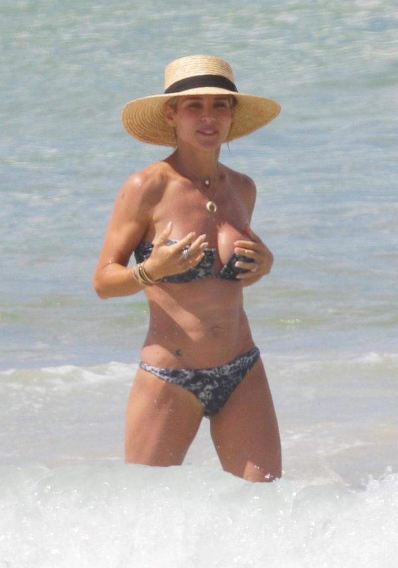 Elsa Pataky did her best to ensure her bikini top wouldn't slip down during a beach day out in Byron Bay. Source: Backgrid