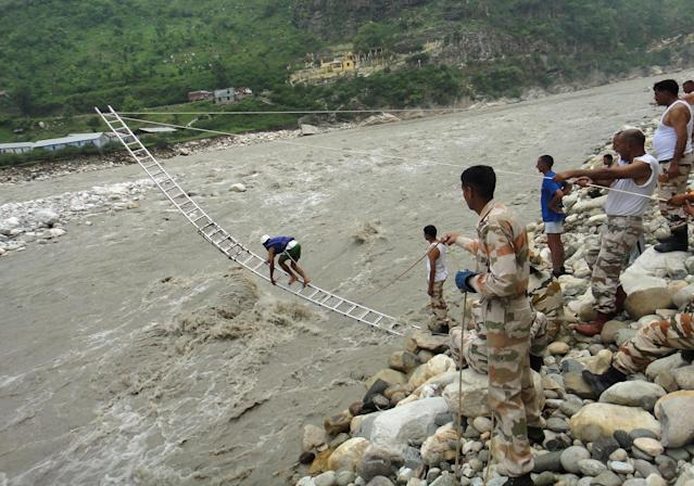 In this handout photograph received from the Indo Tibetan Border Police (ITBP) on June 25, 2013, members of the ITBP rescue stranded people with the help of mountaineering ropes and ladders in Uttarkashi in northern Uttarakhand state. Indian officials stepped up efforts on June 25 to prevent an outbreak of disease in the northern Himalayan region devastated by landslides and flash floods, as rains hampered the rescue of thousands still stranded. AFP PHOTO/ITBP