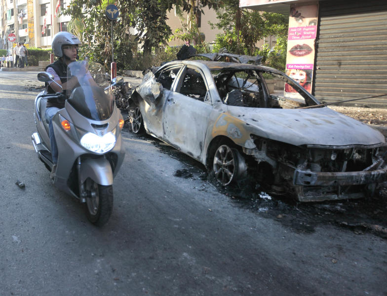 A Lebanese man rides his scooter as he takes pictures of a burned car that was damaged during clashes between pro- and anti-Syrian Sunni groups, in Beirut, Lebanon, Monday May 21, 2012. Gunmen fired rocket-propelled grenades and machine guns early Monday in intense street battles in the Lebanese capital, wounding and killed several people as fears mounted that the conflict in neighboring Syria was bleeding across the border. The clashes erupted hours after an anti-Syrian cleric and his bodyguard were shot dead in northern Lebanon.(AP Photo/Hussein Malla)