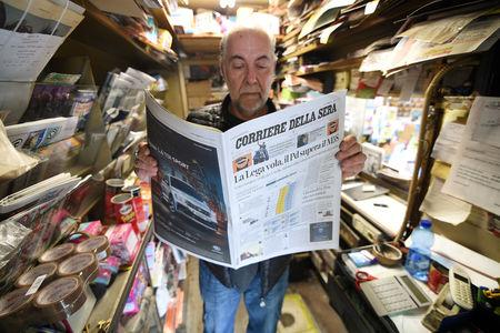 A man reads a newspaper with news of the rise of the far-right League party in Sunday's European parliamentary election in Milan, Italy May 27, 2019. REUTERS/Guglielmo Mangiapane