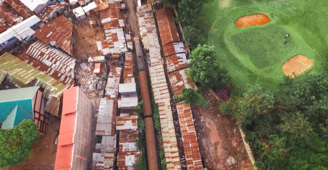 <p>People play golf just across where others are surviving in ramshackle shelters in Nairobi (MediaDrumWorld/Johnny Miller) </p>
