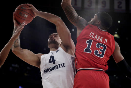Marquette forward Theo John (4) goes up for a shot against St. John's forward Marvin Clark II (13) during the first half of an NCAA college basketball game in the Big East men's tournament, Thursday, March 14, 2019, in New York. (AP Photo/Julio Cortez)