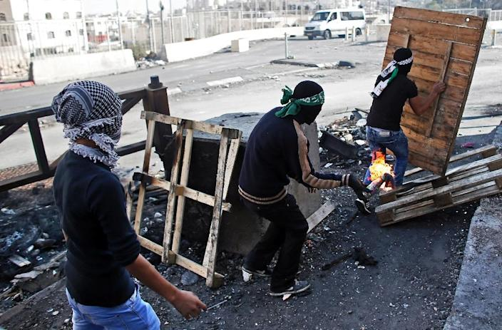 Palestinian demonstraters throw molotov cocktails towards Israeli security forces as they stand next to the separation wall during clashes in the Shuafat refugee camp in east Jerusalem, on October 9, 2015 (AFP Photo/Thomas Coex)