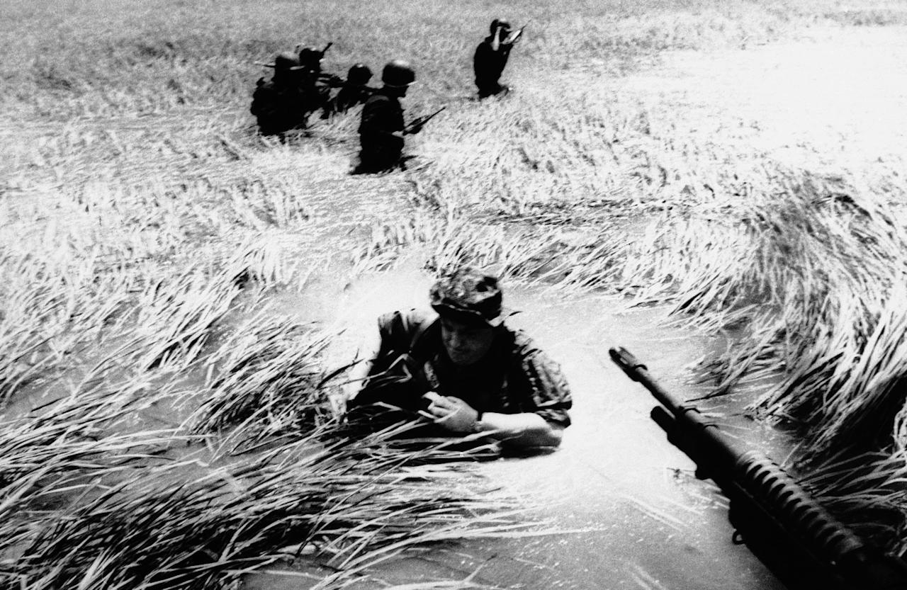 FILE - In this May 11, 1965 file photo, Associated Press photographer Horst Faas tries to get back on a U.S. helicopter after a day out with Vietnamese rangers in a flooded plain of reeds. Faas, a prize-winning combat photographer who carved out new standards for covering war with a camera and became one of the world's legendary photojournalists in nearly half a century with The Associated Press, died Thursday May 10, 2012. He was 79. (AP Photo/File)