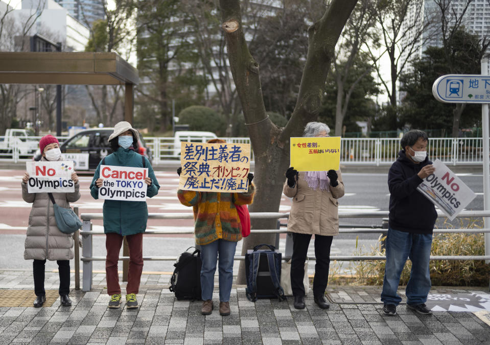Demonstrators hold placards to protest against holding the planned Tokyo 2020 Olympic games in Tokyo on Friday, Feb. 12, 2021. Yoshiro Mori resigned Friday as the president of the Tokyo Olympic organizing committee following sexist comments implying women talk too much. (AP Photo/Hiro Komae)