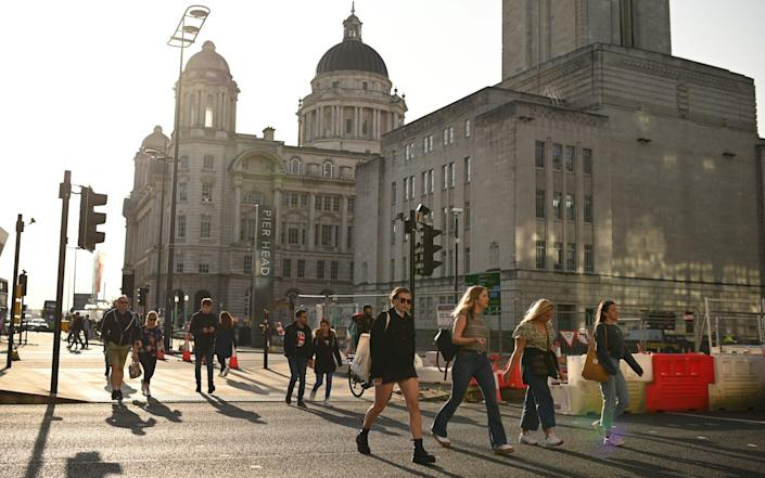 People walk in the early evening sunshine on the Pier Head in Liverpool, north-west England on September 18, 2020 after the British government imposed fresh restrictions on the city after an rise in cases of the novel coronavirus - Oli Scarff/AFP