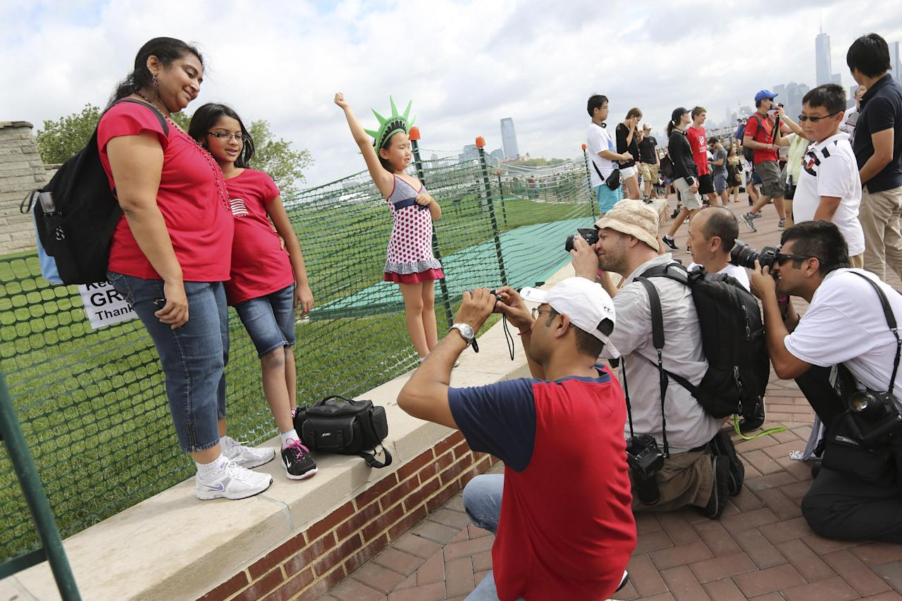 Photographers take photos of people posing for pictures a the base of the Statue of Liberty, Thursday, July 4, 2013 at in New York. The Statue of Liberty finally reopened on the Fourth of July months after Superstorm Sandy swamped Liberty Island in New York Harbor as Americans across the country marked the holiday with fireworks and barbecues. (AP Photo/Mary Altaffer)