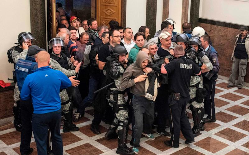 Police officers try to contain protesters as they force their way into Macedonia's parliament  - Credit: AFP