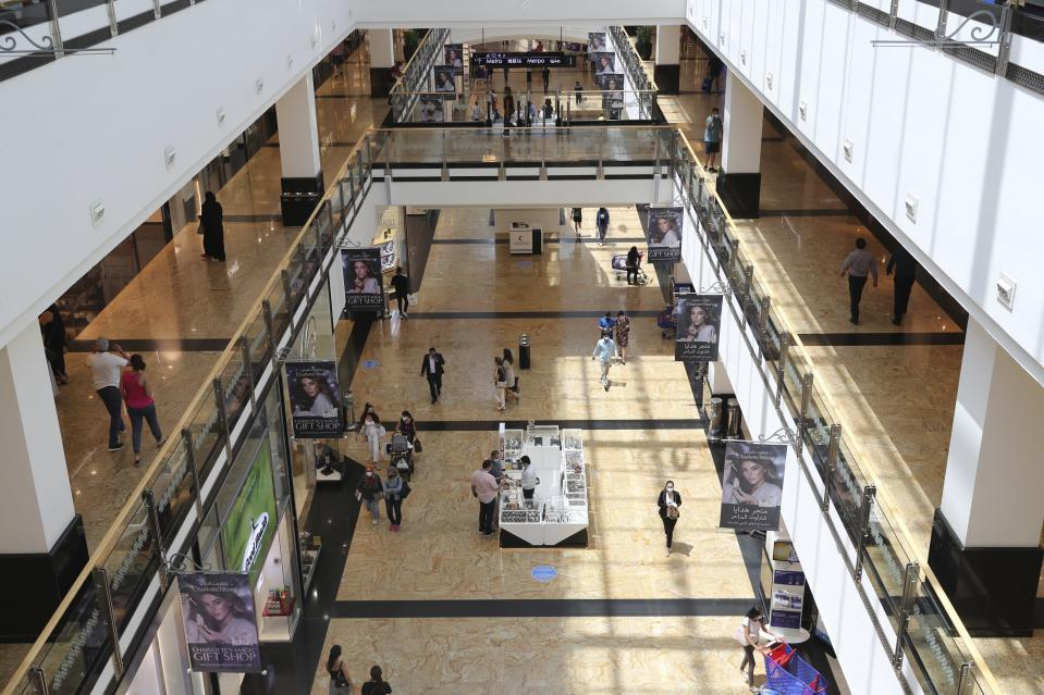 People walk at Mall of the Emirates in Dubai, United Arab Emirates, Thursday, April 15, 2021. The Middle East's largest operator of malls, Majid Al Futtaim, expects revenue and earnings to climb back to pre-pandemic levels by the end of next year and is moving full steam ahead with plans to develop its biggest mall ever. (AP Photo/Kamran Jebreili)