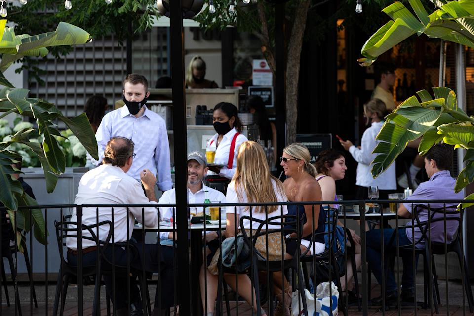 A server converses with people at a crowded restaurant amid a coronavirus disease (COVID-19) outbreak in Birmingham, Michigan, U.S., June 30, 2020