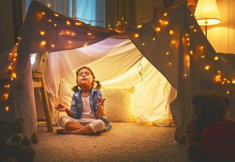 A girl meditates under a sheet covered in lights
