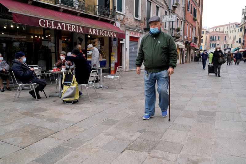 FILE PHOTO: People wearing masks walk on a street, as the number of people infected by the coronavirus disease (COVID-19) continues to rise, in Venice