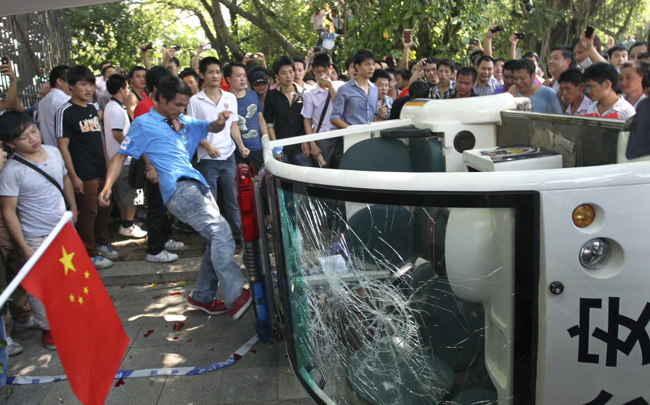 A Chinese demonstrator kicks a broken police vehicle during a protest against Japan in Shenzhen, China Sunday, Sept. 16, 2012. Protesters in China began another day of demonstrations against Japan, after protests over disputed islands spread across numerous cities and at times turned violent. (AP Photo/Apple Daily) HONG KONG OUT, TAIWAN OUT, NO SALES