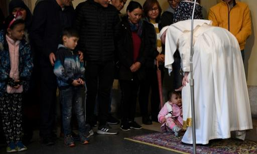 Pope Francis (R) blesses a toddler during an audience with refugees who arrived in Italy from the Greek island of Lesbos