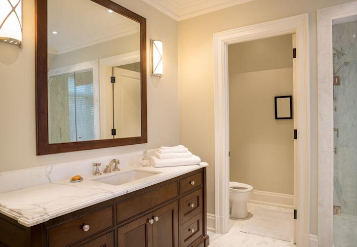 """<p>If you have a boring mirror, this is a great way to make it one of a kind, according to <a href=""""http://getprotip.com/"""" rel=""""nofollow noopener"""" target=""""_blank"""" data-ylk=""""slk:ProTip"""" class=""""link rapid-noclick-resp"""">ProTip</a> resident handyman and pro Rob Shaw. You'll need a chop saw, construction adhesive, and eye protection. First, choose a trim that would look amazing around the mirror edges. Measure the dimensions of your mirror, noting the longest measurements from corner to corner. </p><p>Set the chop saw's table to a 45 degree angle and cut. Be mindful that you will need to move the table to -45 degrees for the next cut, you should end up with a 45 and -45 cut on each piece for perfectly joined corners. Size up your pieces before applying adhesive and paint, and decorate accordingly. Then apply construction adhesive to the back of trim pieces and use masking tape to hold them in place starting low and finishing with your top piece last.<br></p>"""