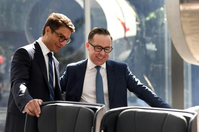 Qantas CEO Alan Joyce (R) and CFO Tino La Spina inspect the premium economy seats for the airline's new 787-9 Dreamliner, after a press conference in Sydney, on February 23, 2017