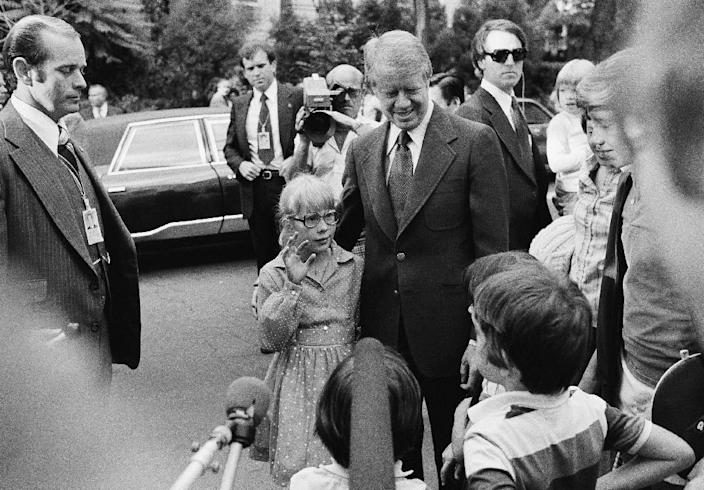FILE - In this June 8, 1977 file photo, President Jimmy Carter stands with his daughter Amy as she waves to other children on the street in the Georgetown section of Washington, guarded by Secret Service agents. Carter went to Georgetown to dine at the home of Management and Budget Director Bert Lance. The Secret Service has been tarnished by a prostitution scandal that erupted April 13, 2012 in Colombia involving 12 Secret Service agents, officers and supervisors and 12 more enlisted military personnel ahead of President Barack Obama's visit there for the Summit of the Americas. (AP Photo/Barry Thumma)