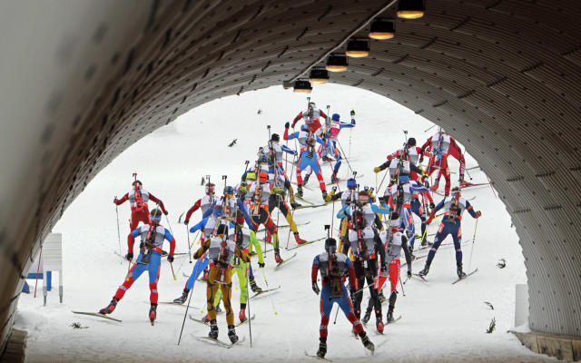 Biathletes exit a tunnel as they compete in the men's 15 km mass start race during the International Biathlon Union (IBU) World Championships in Nove Mesto February 17, 2013. REUTERS/David W Cerny (CZECH REPUBLIC - Tags: SPORT BIATHLON) - RTR3DWYZ