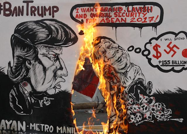 <p>Militant groups burn a mural bearing the image of President Donald Trump and Philippines' President Rodrigo Duterte during a protest against the upcoming visit of Trump in the country for the 2017 ASEAN Summit at Mendiola Bridge in metro Manila, Philippines, Nov. 10, 2017. (Photo: Czar Dancel/Reuters) </p>
