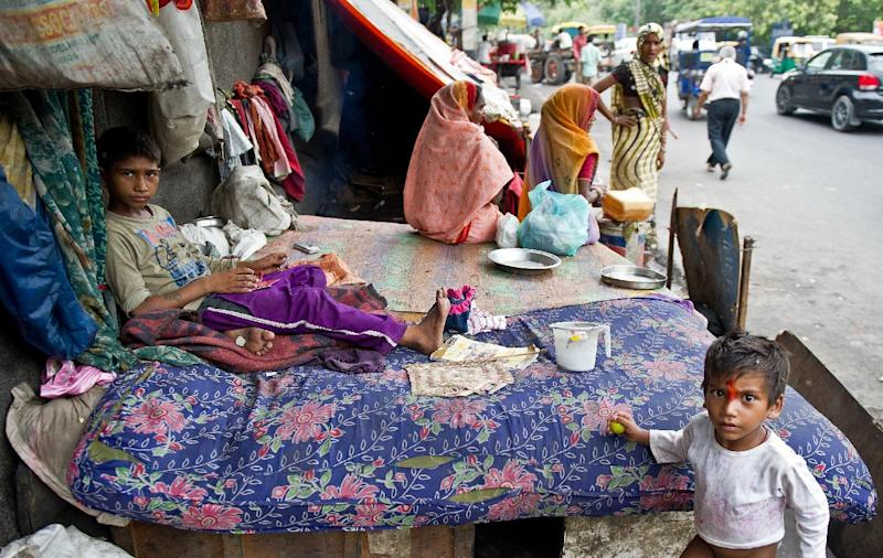Children of a homeless family play by the bed of their roadside shanty in New Delhi on July 22, 2014 (AFP Photo/Prakash Singh)