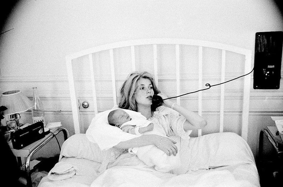 <p>Catherine makes a telephone call from bed after the birth of her newborn son, Christian Vadim, in 1963. The French actress welcomed her firstborn with director, Roger Vadim. </p>