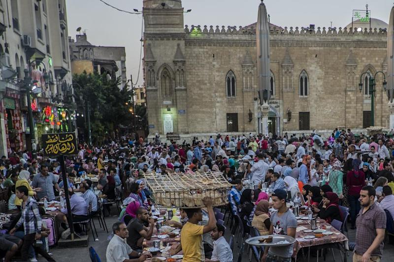 "Egyptian Muslims sit on shared tables as they wait for the ""Iftar"" meal to break their day-long fast during the holy month of Ramadan in Cairo's Khan el-Khalili district, on July 8, 2014 (AFP Photo/Khaled Desouki)"
