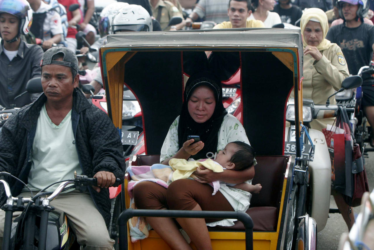 An Acehnese woman checks her mobile phone as she and her baby evacuate to higher ground after a strong earthquake was felt in Banda Aceh, Aceh province, Sumatra island, Indonesia, Wednesday, April 11, 2012. Two massive earthquakes triggered back-to-back tsunami warnings for Indonesia on Wednesday, sending panicked residents fleeing to high ground in cars and on the backs of motorcycles. There were no signs of deadly waves, however, or serious damage, and a watch for much of the Indian Ocean was lifted after a few hours. (AP Photo/Heri Juanda)