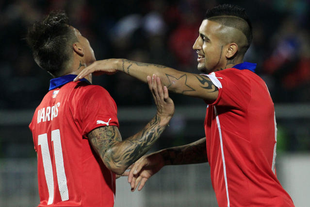 Chile's Arturo Vidal, right, celebrates with Eduardo Vargas after scoring against Northern Ireland during a friendly soccer match, in Valparaiso, Chile, Wednesday, June 4, 2014. (AP Photo/Luis Hidalgo)