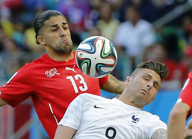 Switzerland's Ricardo Rodriguez, left, and France's Olivier Giroud battle for the ball during the group E World Cup soccer match between Switzerland and France at the Arena Fonte Nova in Salvador, Brazil, Friday, June 20, 2014. (AP Photo/David Vincent)