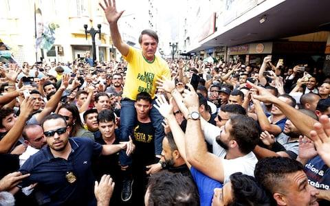 Jair Bolsonaro is taken on the shoulders of a supporter moments before being stabbed - Credit: Antonio Scorza