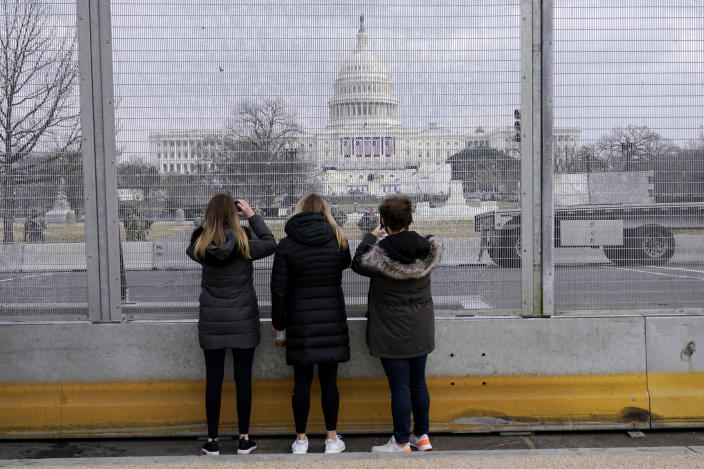 People take photos through the extensive security surrounding the U.S. Capitol in Washington, Friday, Jan. 15, 2021, ahead of the inauguration of President-elect Joe Biden and Vice President-elect Kamala Harris. (AP Photo/Susan Walsh)