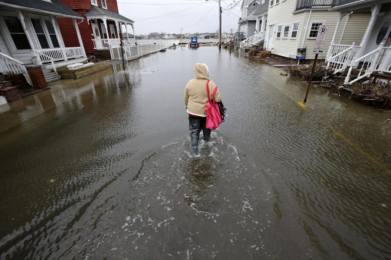 Carol Marelli walks down her flooded street Thursday, March 7, 2013, in Sea Bright, N.J., after an overnight storm. Flooding remained a problem in other shore towns. Water on roadways was also forcing closures in towns including Monmouth Beach, Absecon, Aberdeen, Egg Harbor Township and Wildwood. A coastal flood warning remains in effect until 9 a.m. Friday, but forecasters were not expecting Thursday's wind to be as strong as Wednesday, when gusts exceeding 60 mph were recorded in many places along the ocean. (AP Photo/Mel Evans)