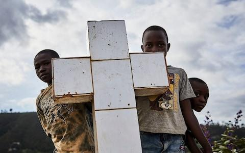Local boys look at the funeral of Ebola victims - 1,147 people have so far died - Credit: HUGH KINSELLA CUNNINGHAM/EPA-EFE/REX